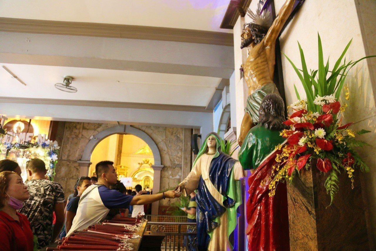 許多信徒也會到耶穌受難像底下摸使者手以祈求心願達成。記者魏妤庭/攝影