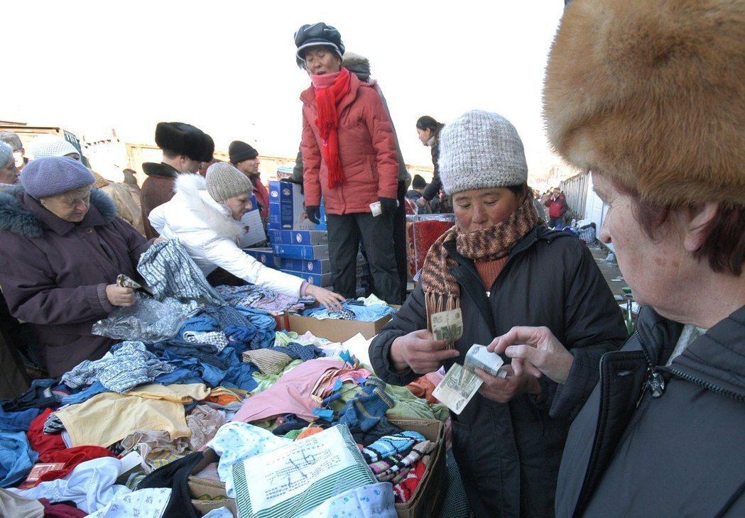 遠東貿易仰賴中國,進口商品主要為機電、紡織等工業製成品。圖為中俄邊境上,中國攤販...