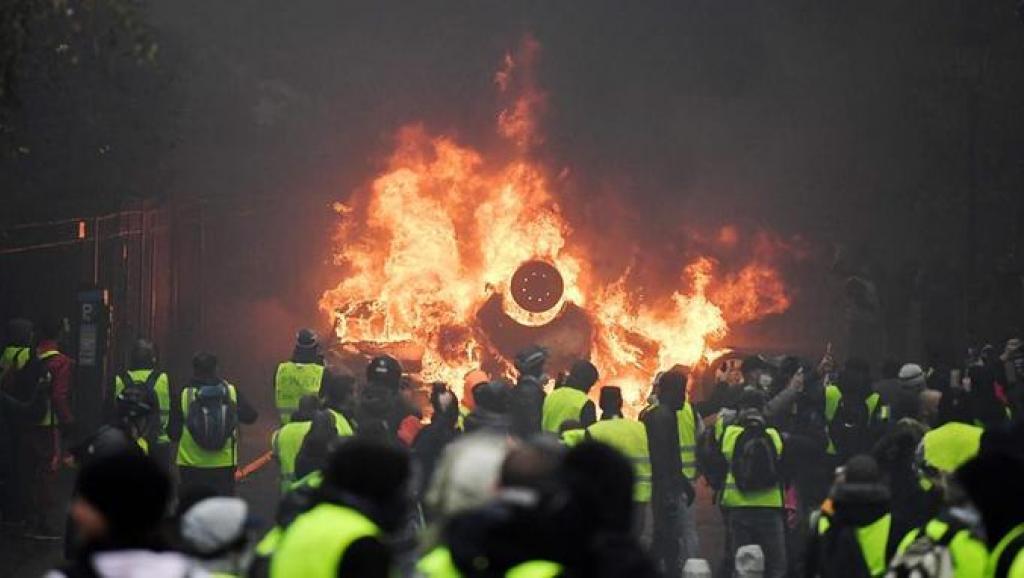 法國「黃背心」運動延燒近兩周,穿著黃背心的民眾放火燒車。路透