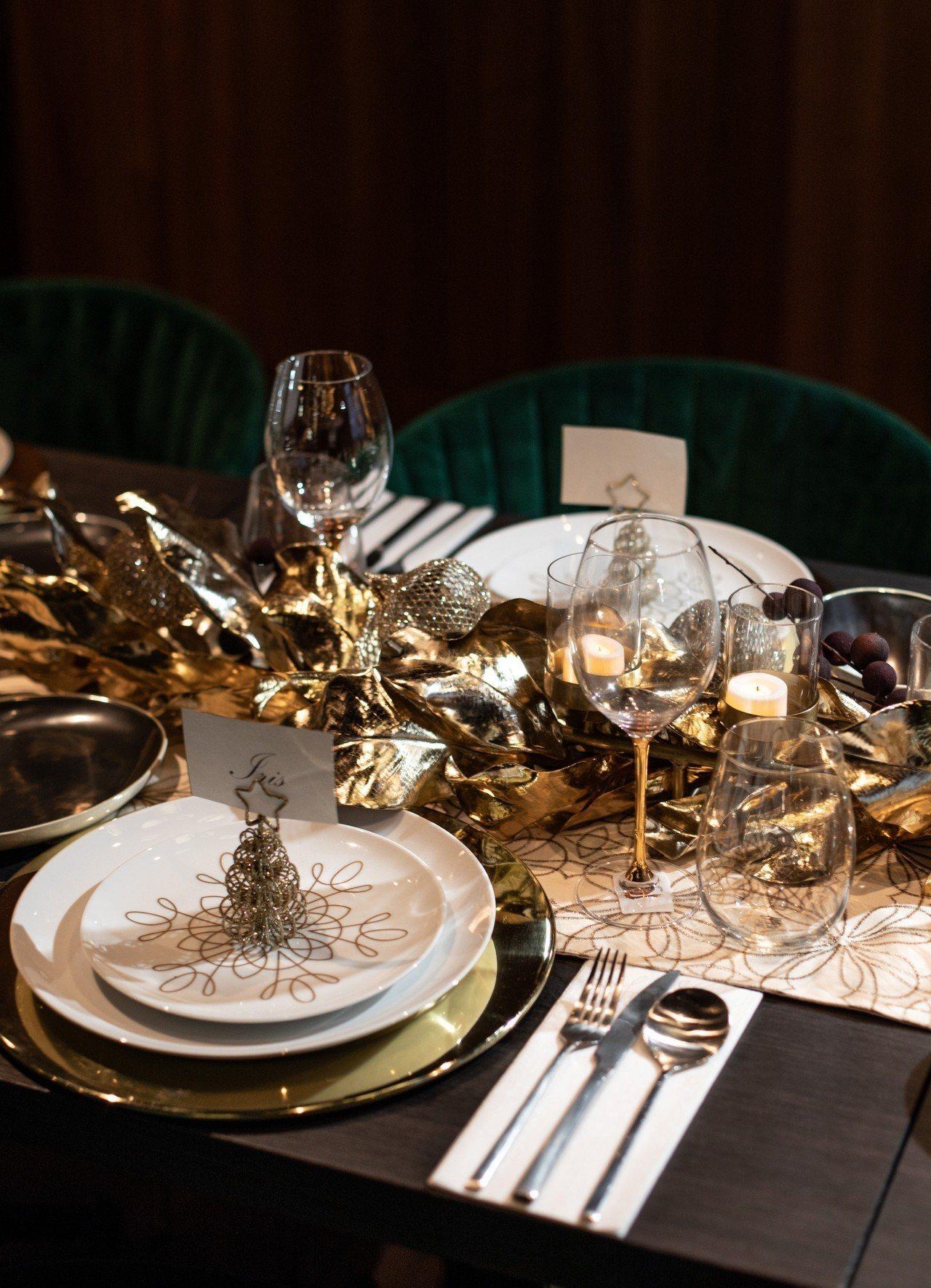 餐桌佈置以閃亮金色木蘭花與紫漿果花環穿繞於黃銅線形茶蠟燭臺間作為桌面重點裝飾;餐...