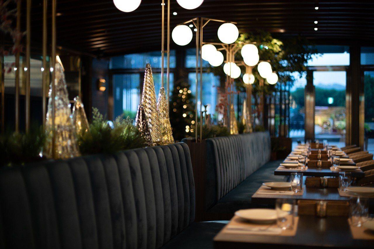 沙發座位區的狹長平台巧妙地放上栩栩如真的松枝花環,錯落搭配金、銀聖誕樹燈飾、燭臺...