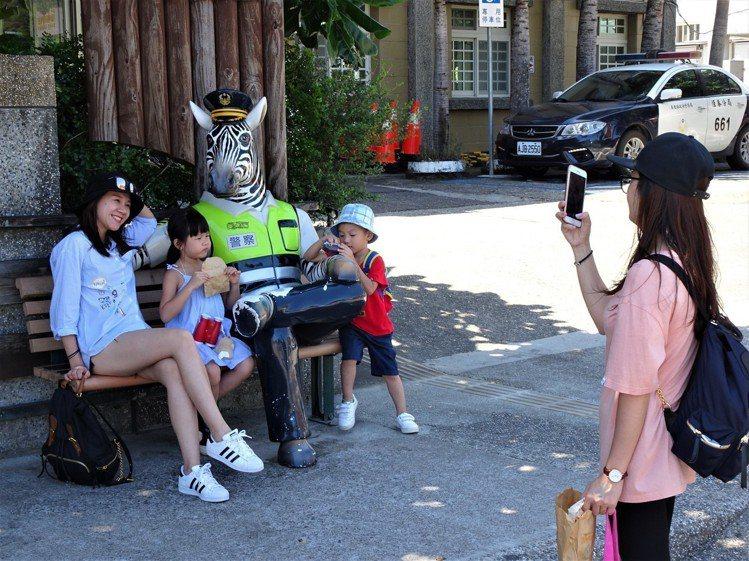 斑馬警察先生蹺腿坐在墾丁派出所門外長椅,吸引中外遊客合照。圖/記者潘欣中攝影