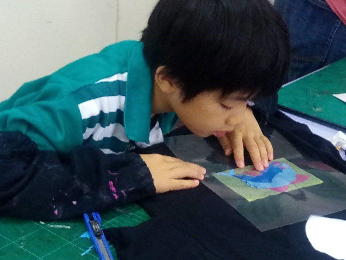 淡水國小美術班小朋友運用絹印的方式來製作班服,將淡水漁港特色的圖案,印到素色的衣...