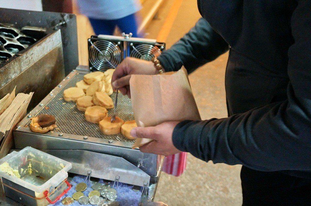 站前梅花雞蛋糕的客人早已習慣幫剛烤好的雞蛋糕搧風、裝袋、還自己找錢。圖/踢小米提...