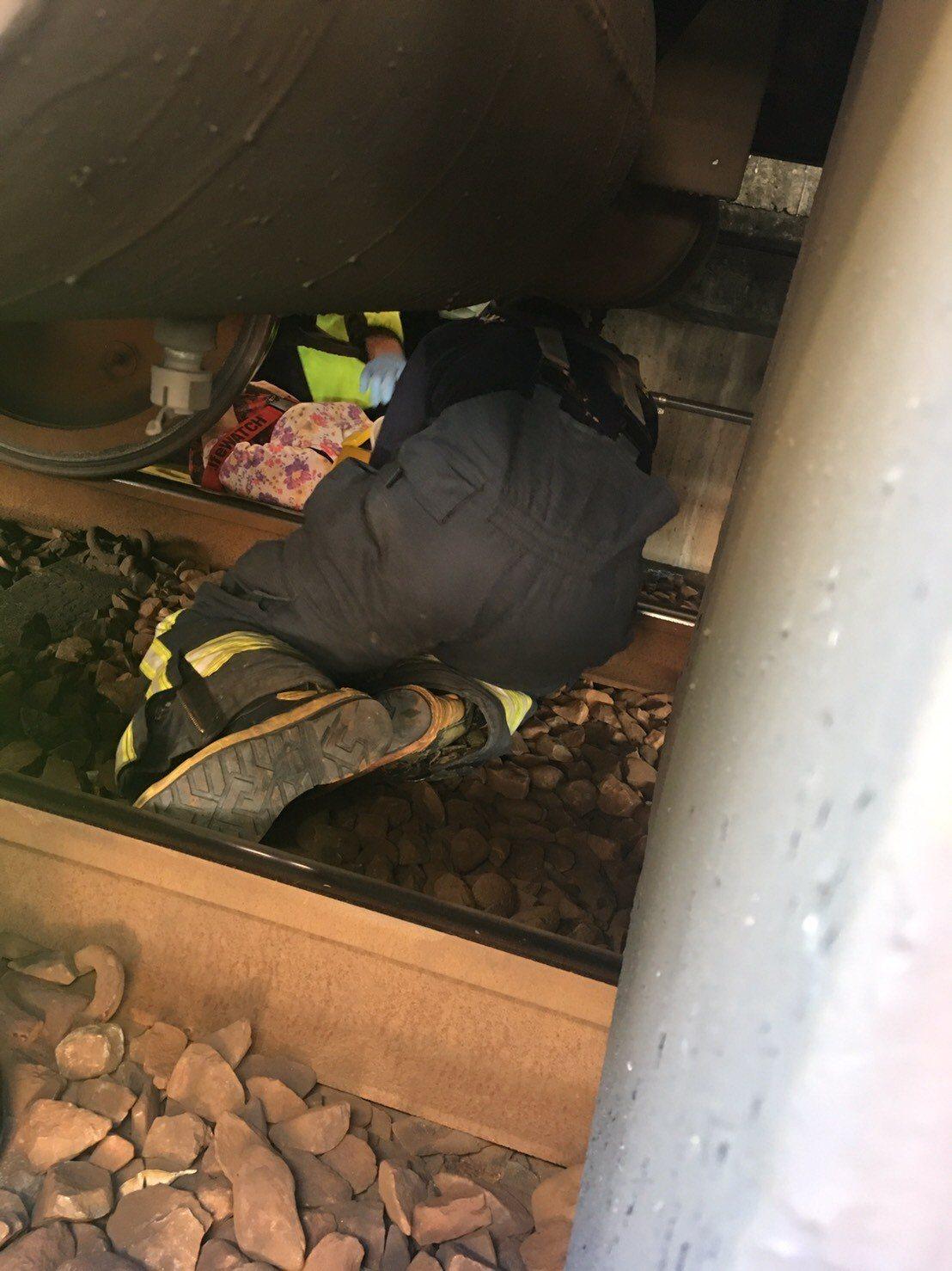 台鐵樹林站婦人落軌 所幸當時列車緊急煞住,消防人員趴在車底救人。圖/新北市消防局...