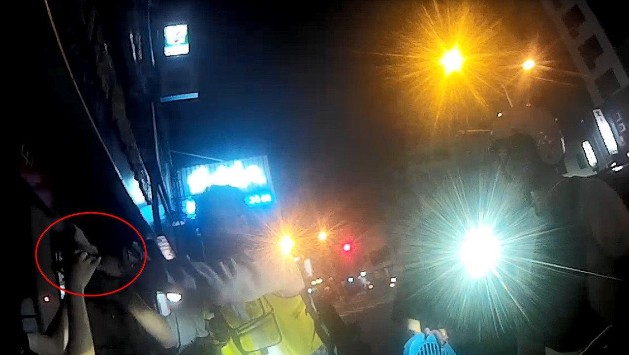 現場民眾以手機協助打燈、拆卸機車零件,警民合作順利救出受困小貓(紅色圓圈處)。記...