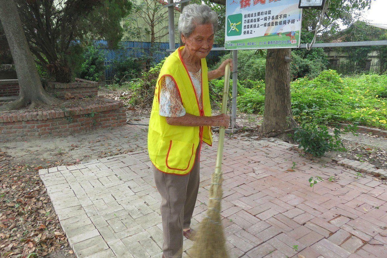 台南市佳里區漳洲社區環保義工隊91歲的阿嬤楊竅,扭傷腳看到落葉,仍忍不住拿掃把掃...