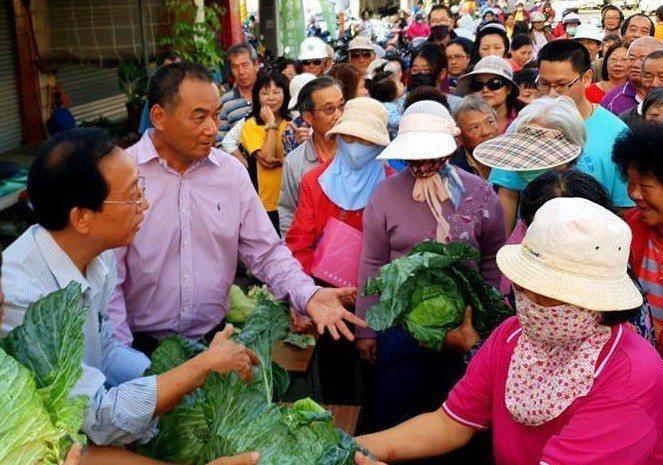 台南市議員謝財旺(左二)與好友收購10萬台斤高麗菜分贈給鄉親,下午吸引大批民眾排...