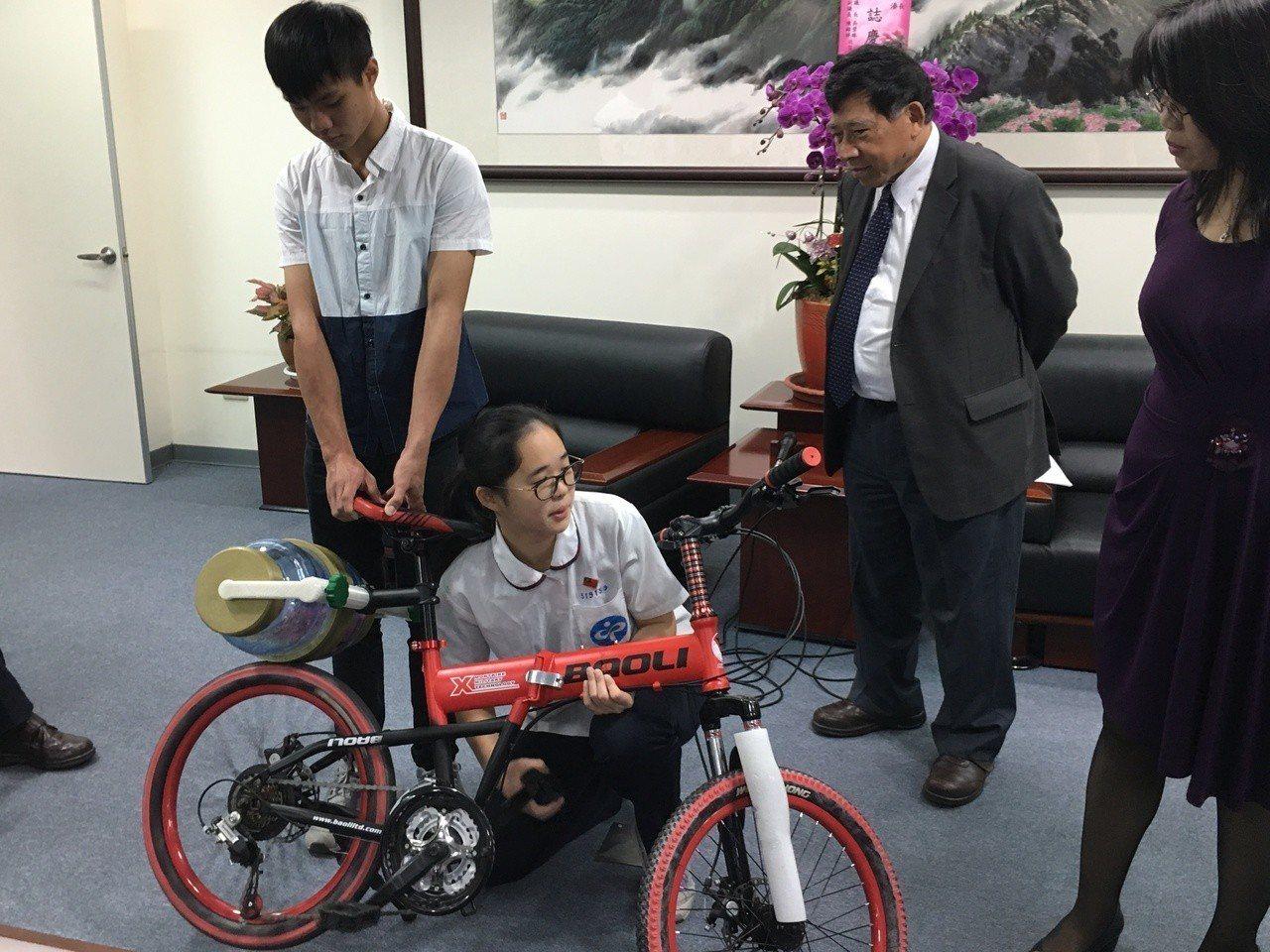 暨大附中簡詩婷同學親自操作自行車滾桶洗衣設備。記者張家樂/攝影