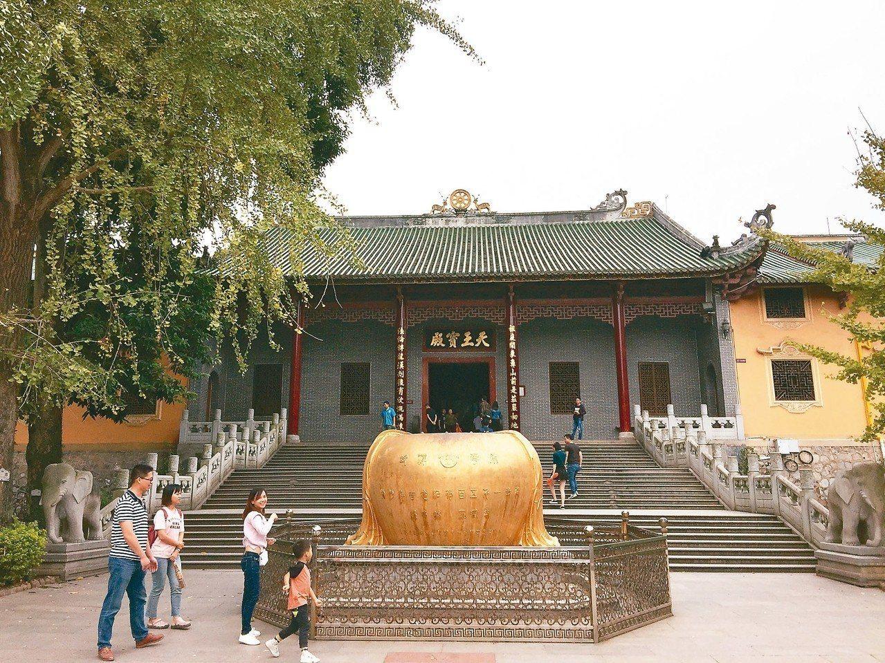 天王寶殿前廣場的金色衣缽,信眾投錢入內,祈福許願。 記者汪莉絹/攝影