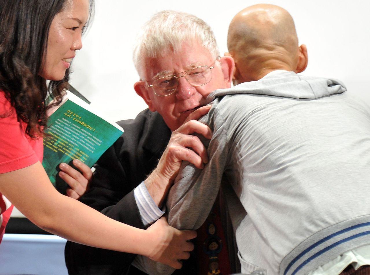 羅慧夫(中)2013年出席感恩見面會,患者激動擁抱他。 圖/聯合報系資料照片