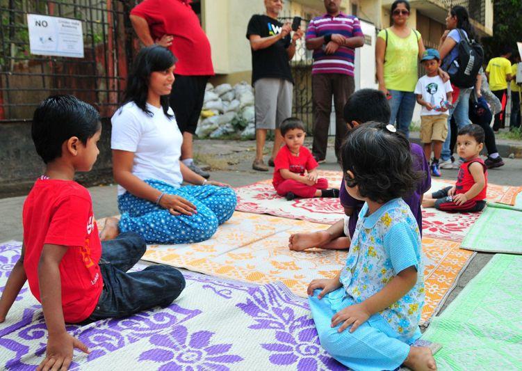 印度孟買,一名瑜伽俱樂部的老師在教參加活動的兒童練習瑜伽。新華社