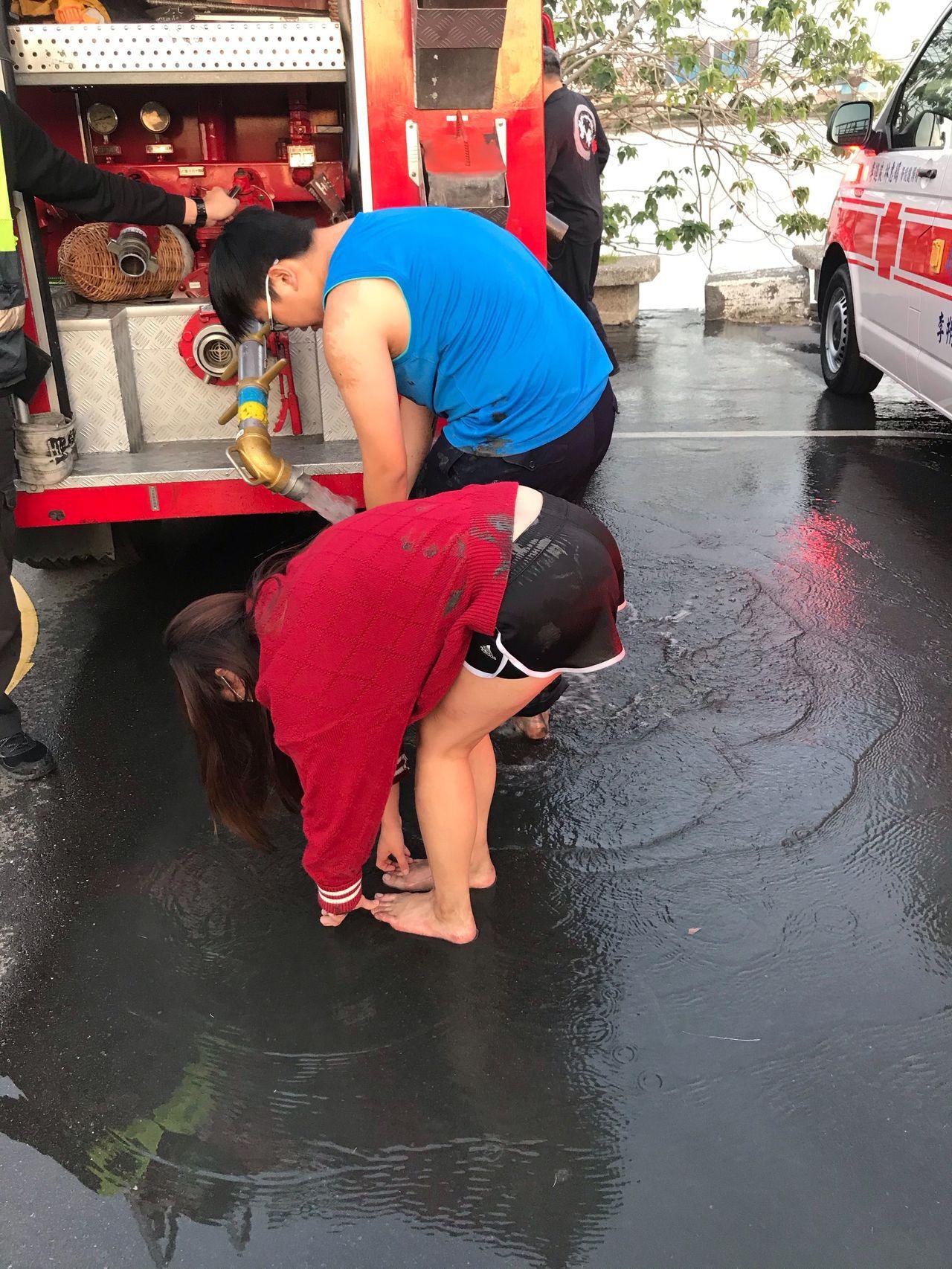 消防車供水讓2人清洗汙泥。記者林昭彰/翻攝