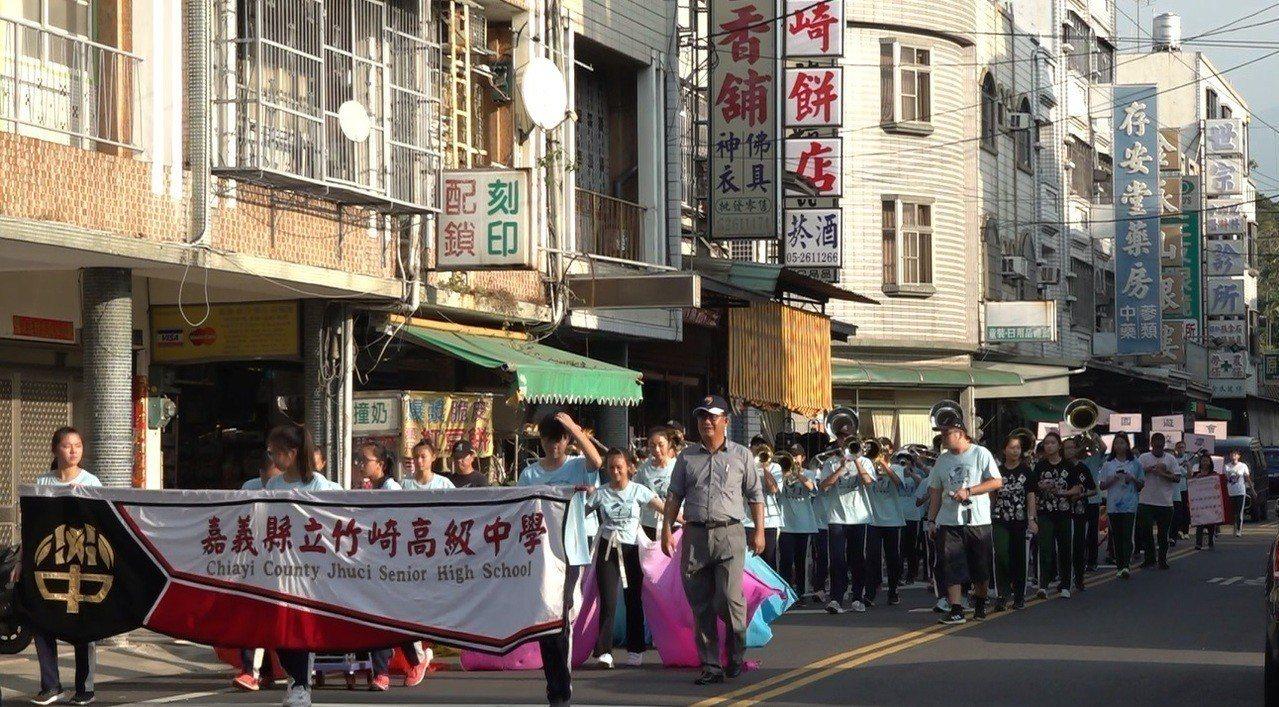竹崎高中樂旗隊在竹崎街上踩街,宣傳12/8周六舉行的校慶「無塑」園遊會。記者謝恩...