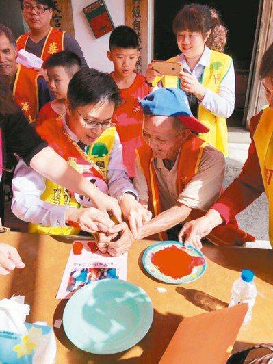 南投市漳興國小昨天製作大卡片贈送給獨居的林姓阿公(右),讓老人家相當開心。 圖/華山基金會提供