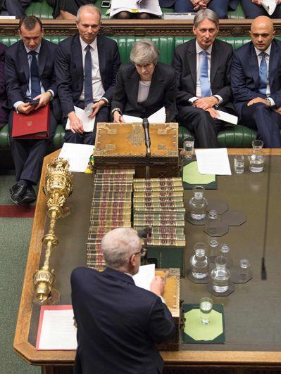英國首相梅伊(中)在國會聽取工黨領袖柯賓(前)發言。 (法新社)