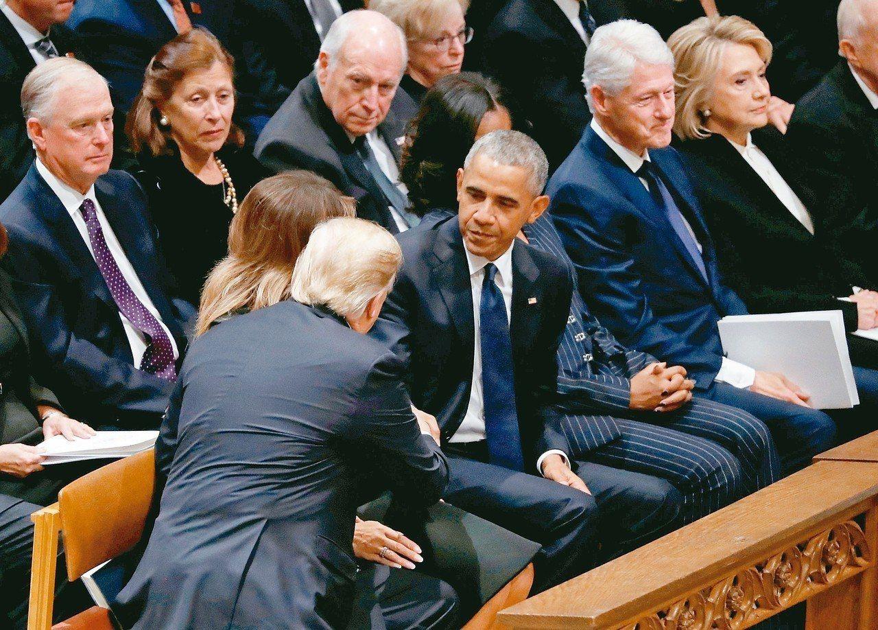 美國總統川普(左)5日參加前總統老布希喪禮,入座時主動伸手和他的前任歐巴馬握手,...