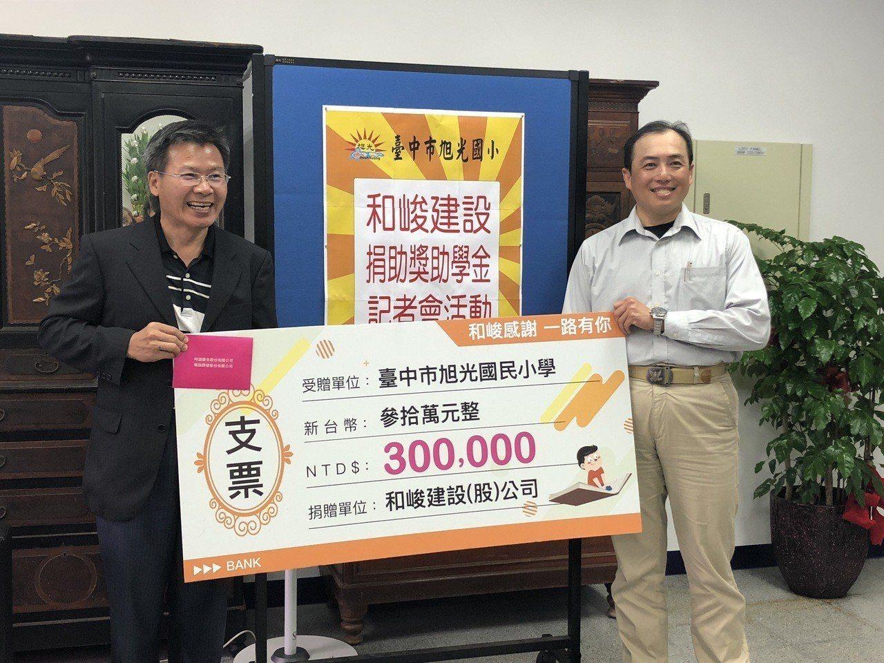 和峻建設副理張展溢(右)代表捐贈30萬元奬學金給旭光國小校長許慶昌(左)。記者宋...