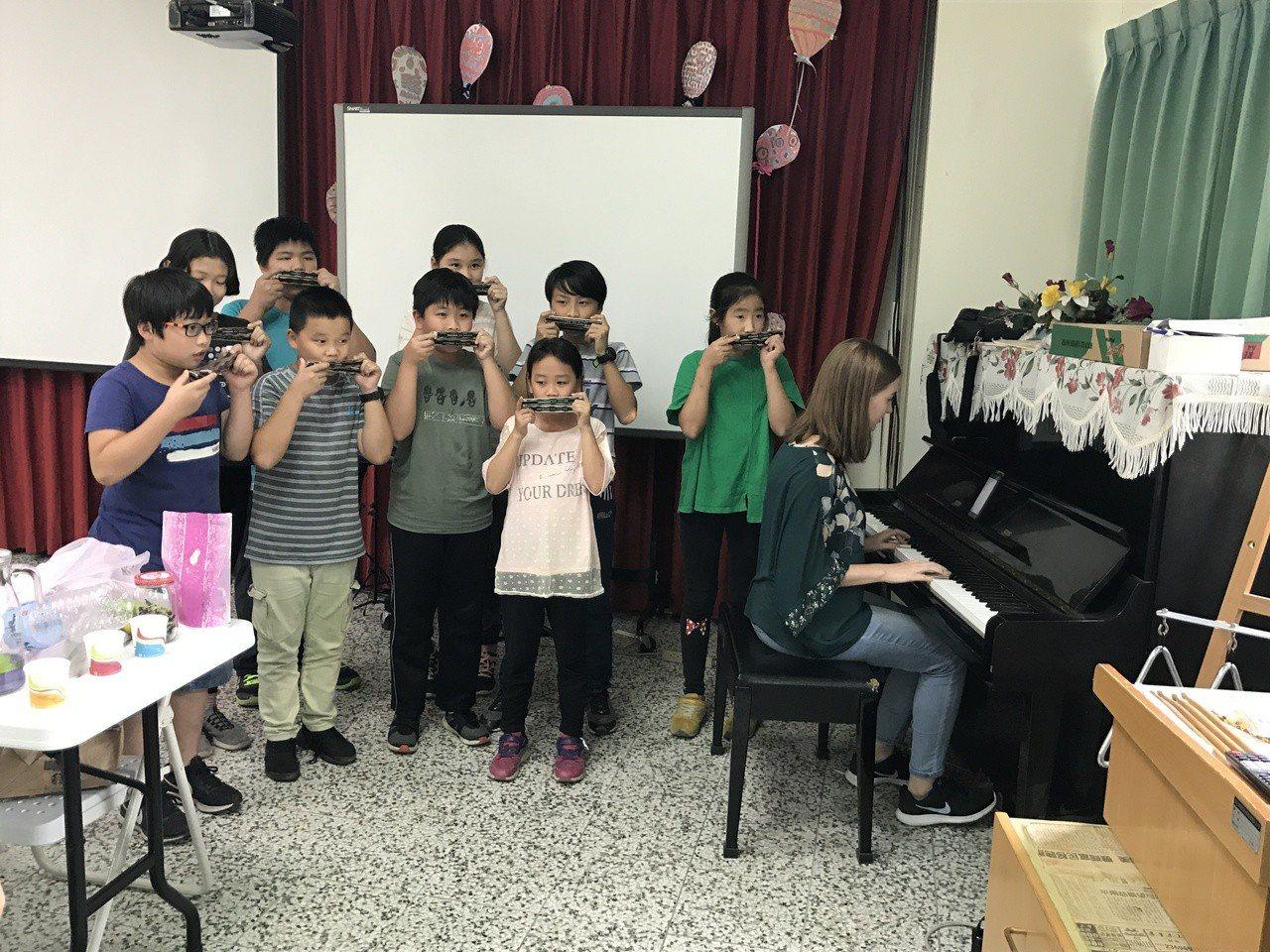 俄羅斯大學生翁蔡文(右1)彈鋼琴,長福國小學生則吹口琴,雙方合奏俄羅斯民謠。圖/...