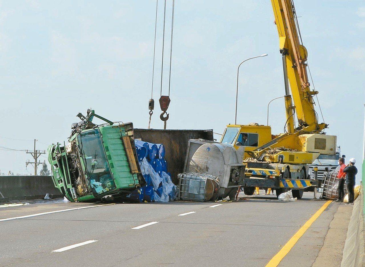 滿載油桶的大貨車昨天上午行經台61線雲林台西路段翻覆,相關單位封路搶救。 記者蔡...
