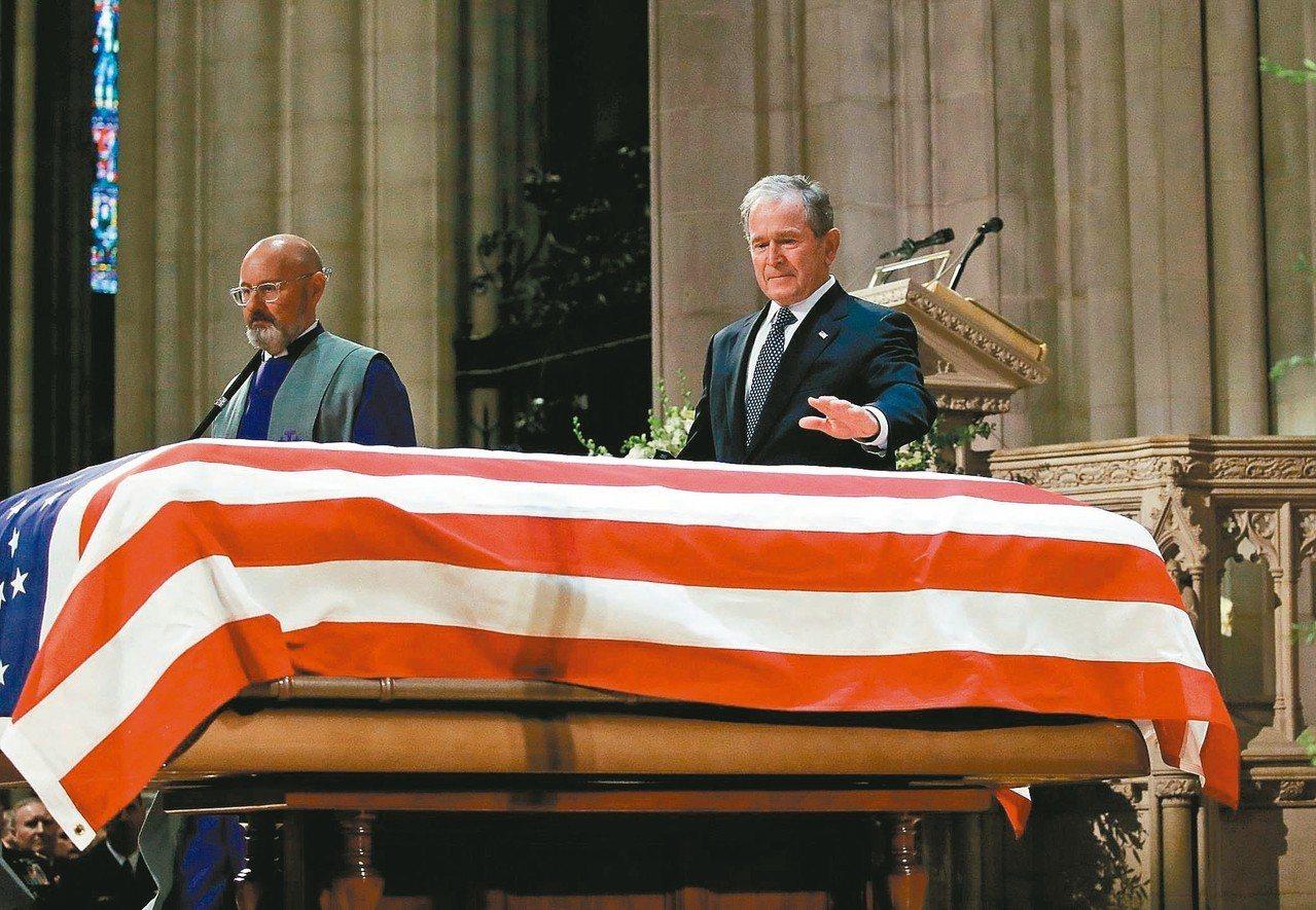 美國前總統小布希(右)五日在國葬儀式上輕撫父親老布希的靈柩。 (法新社)