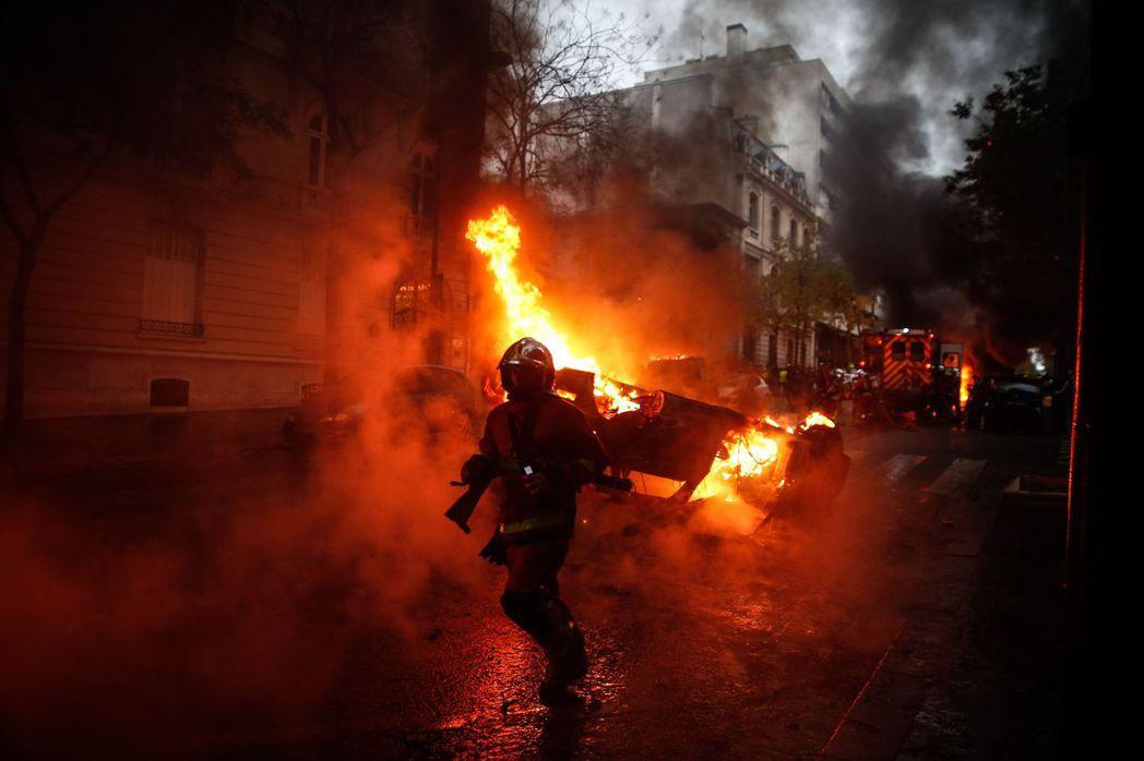 黃背心示威者1日在巴黎縱火燒車,圖為消防員忙著撲滅火勢。 法新社