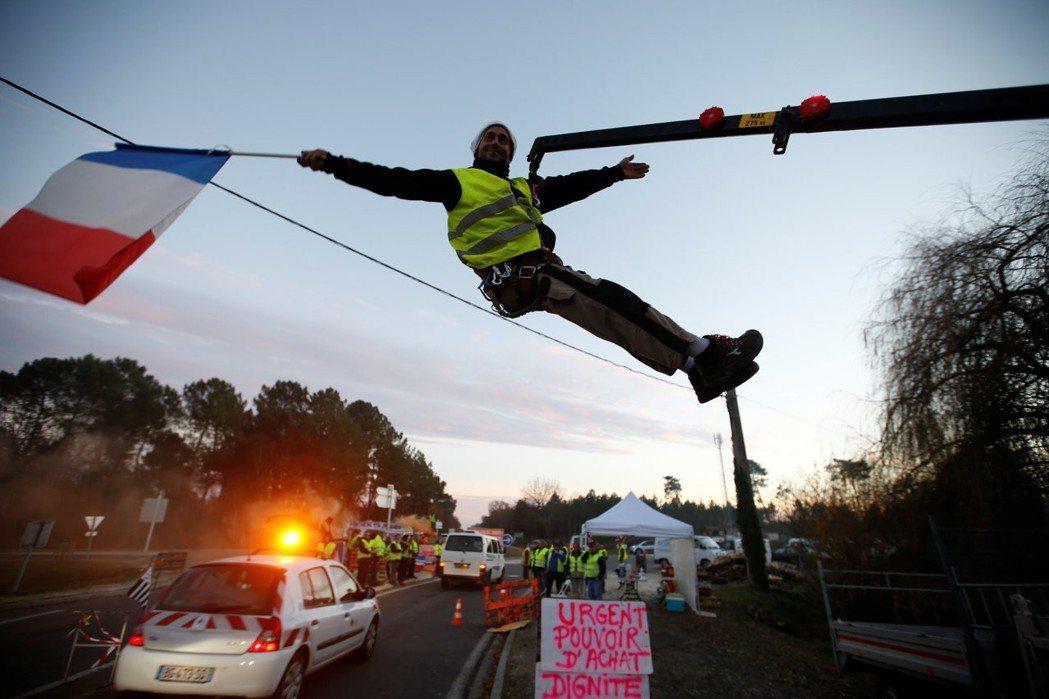 一名黃背心示威者5日在法國西南部西薩克梅多克鎮的路口示威,由吊車吊起,拿著法國國...