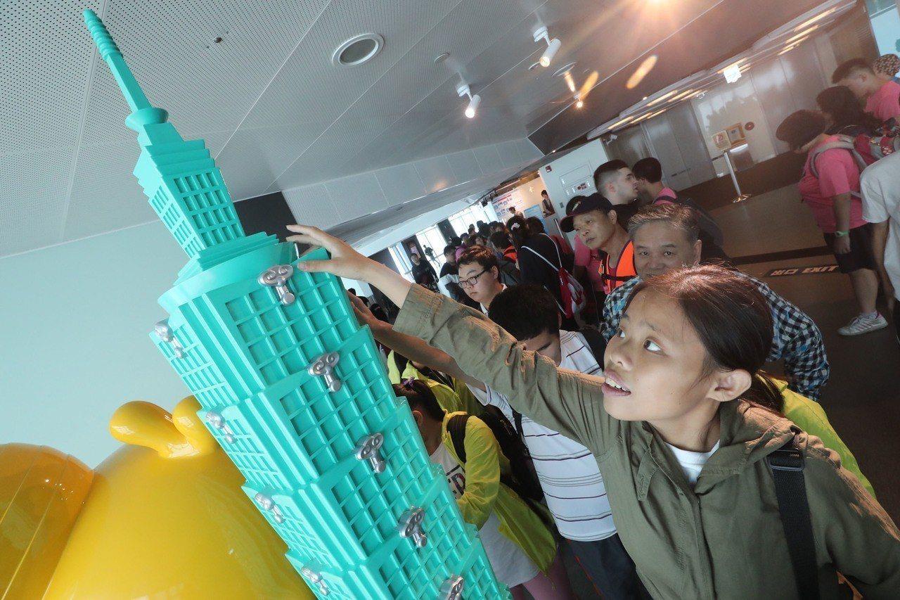 台北市啟明學校學生7日下午在老師及家長陪同下參觀台北101,小朋友用手觸摸感覺1...