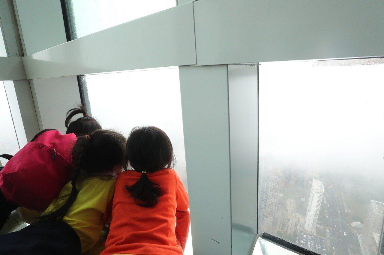 台北市立啟明學校學生7日下午參觀台北101,在觀景台俯瞰台北市景,雖然天氣不佳、...