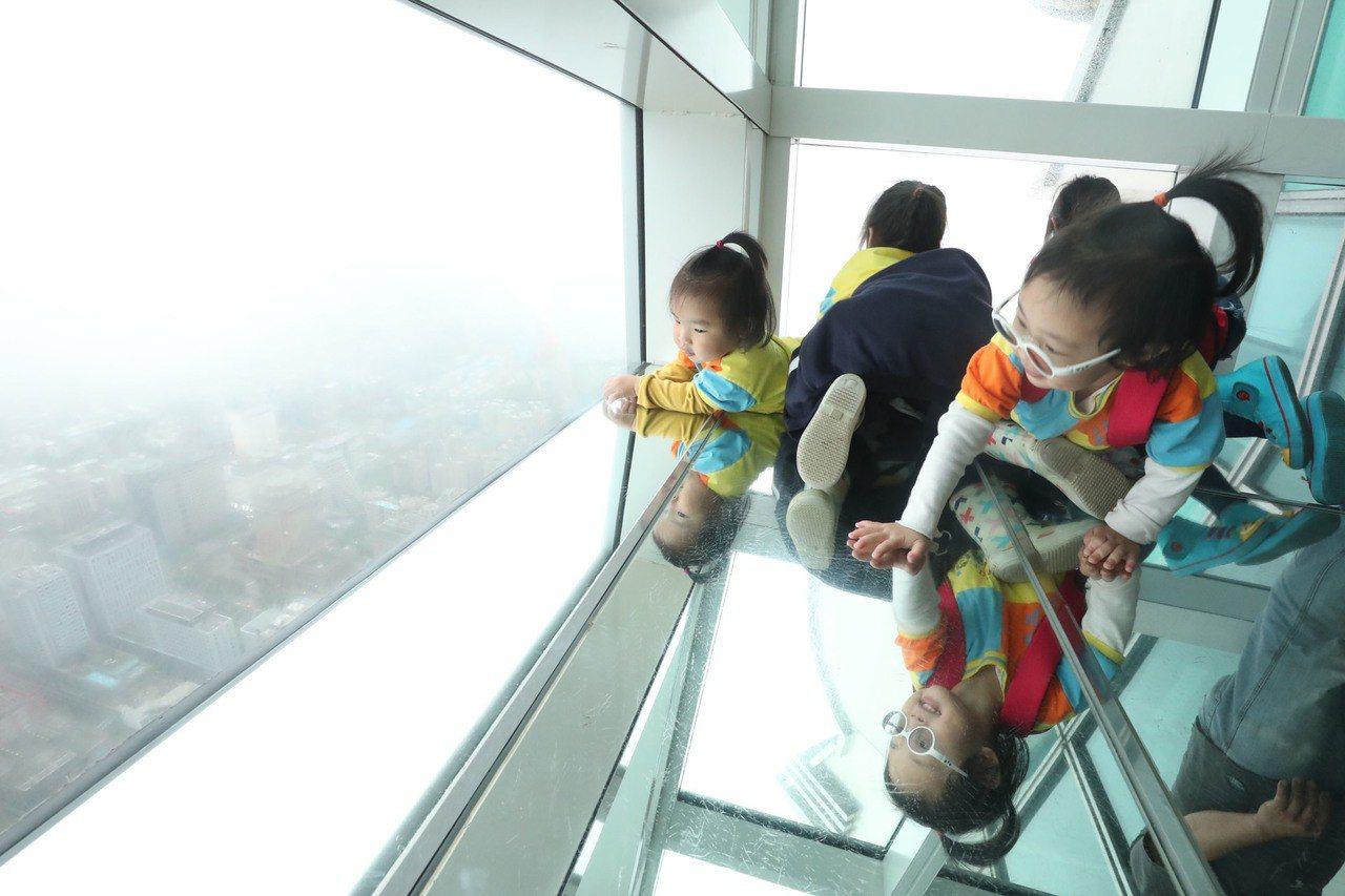 台北市立啟明學校學生7日下午參觀台北101,在觀景台俯瞰台北市景。 中央社