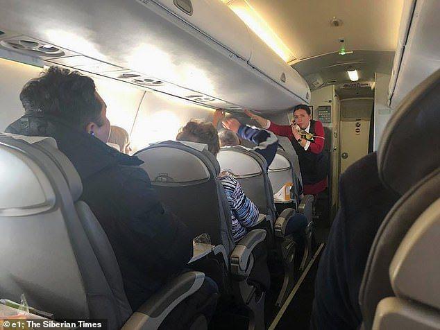 機組員試圖安撫機內旅客。圖擷自今日郵報
