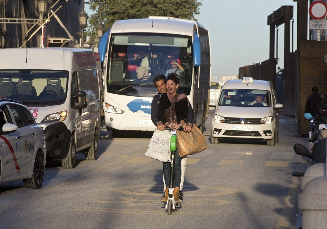 伴隨電動滑板車而來的交通、城市問題,層出不窮。圖為馬德里街頭,違規雙載的某對情侶...