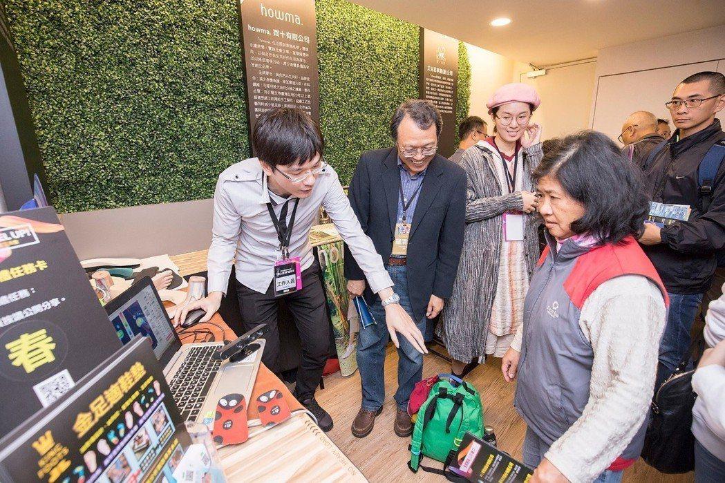 教育部青年發展署羅清水署長(左二)在金足適工作人員解說下與參觀民眾熱情互動。