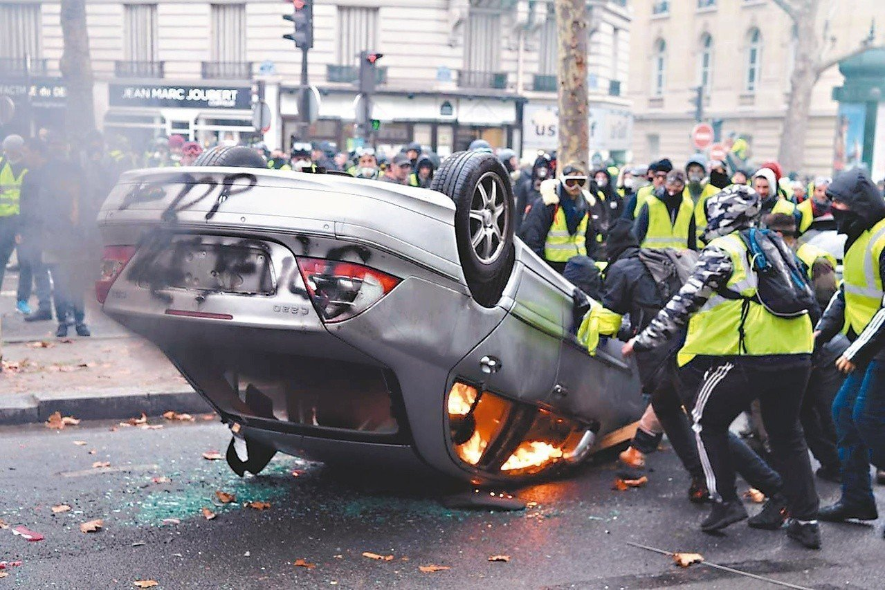 蒙面的黃背心示威者1日在巴黎香榭大道縱火燒車。 法新社