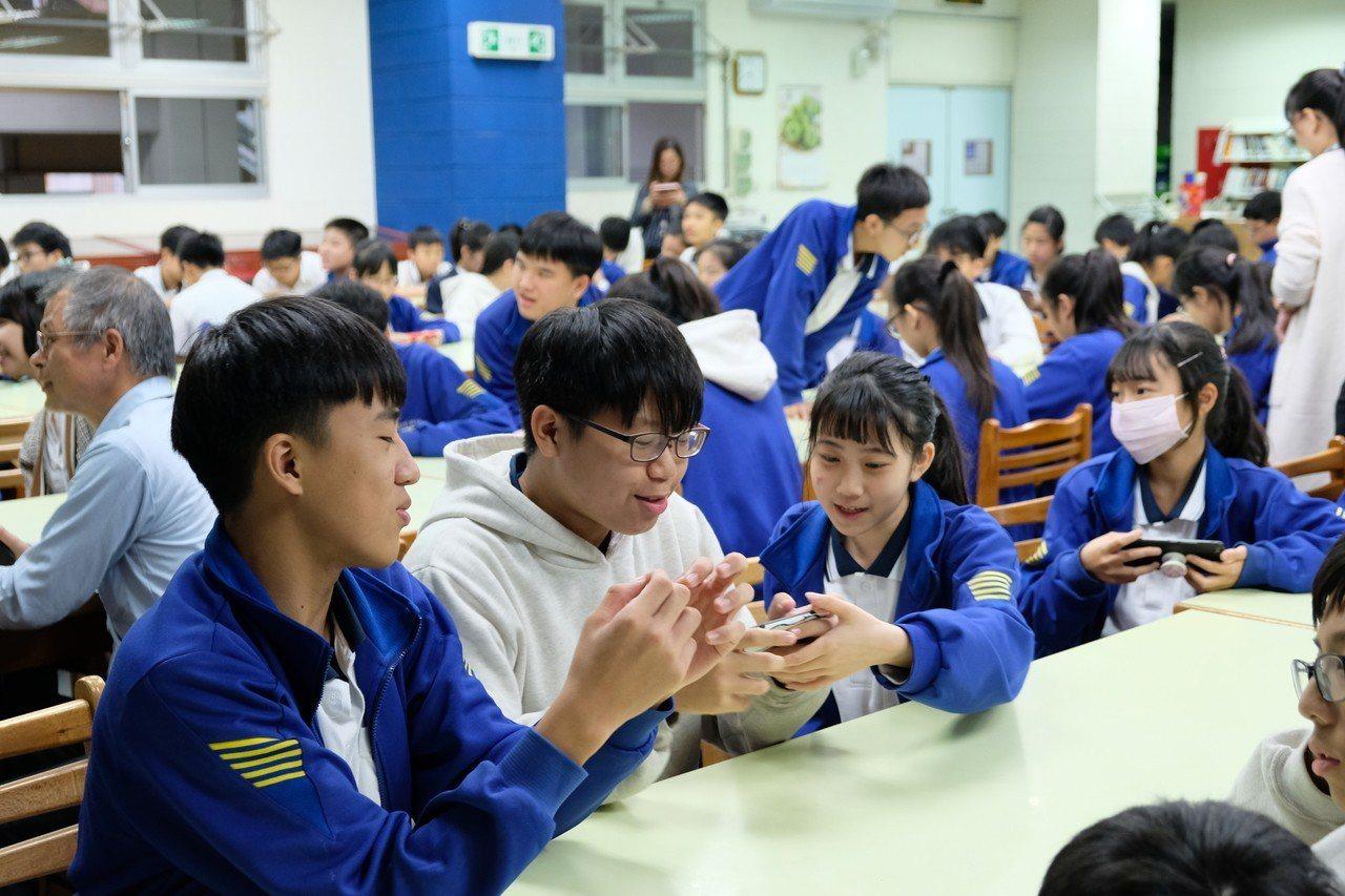 台下學生們拿起手機玩《已毒快快回》,也藉由與同學互相討論、一同學習。記者張曼蘋/...