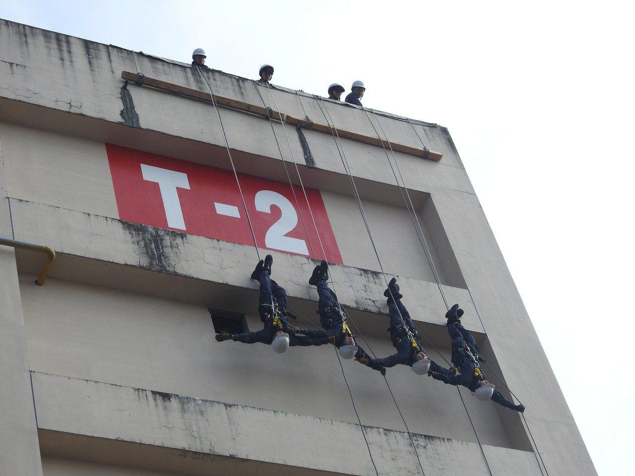 106年消特班今結訓,學員完整倒立式、座位式、斜降、T型救援等高樓層垂降技巧。記...