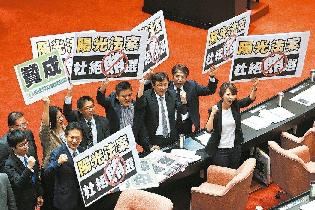 立法院院會進行地方制度法條文修正案表決,民進黨立委舉牌高喊「終結黑金政治、終結議...