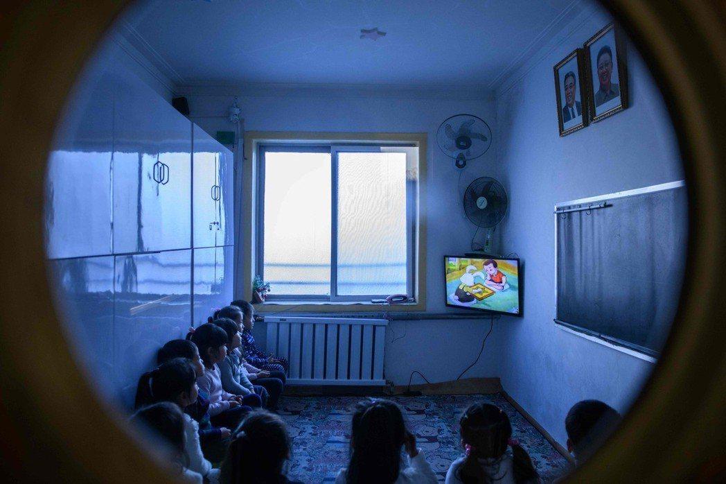 全北韓教室均懸掛金日成父子肖像,圖為新義州幼兒園在教室中觀賞卡通情形。 (法新社...