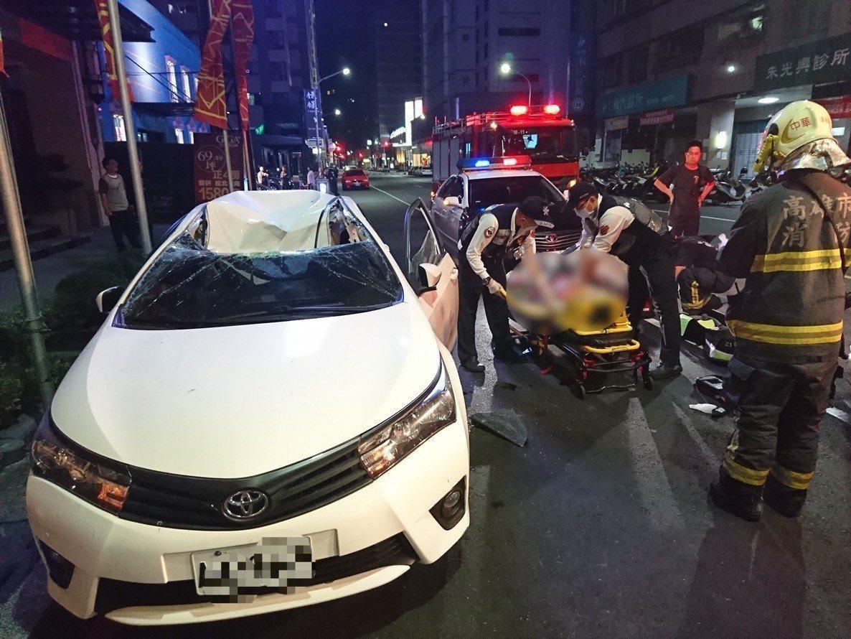 郭姓外籍英文老師墜樓掉進轎車內,正由救護人員送醫。記者林保光/翻攝