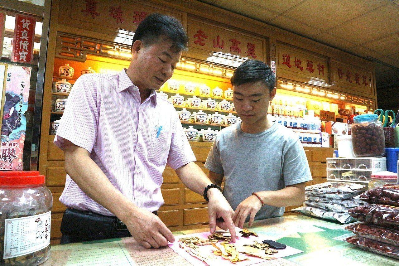 60歲的新店中藥行老闆吳鴻貞(左),從兒子吳昕峰(右)小時候即手把手教導兒子辨認...
