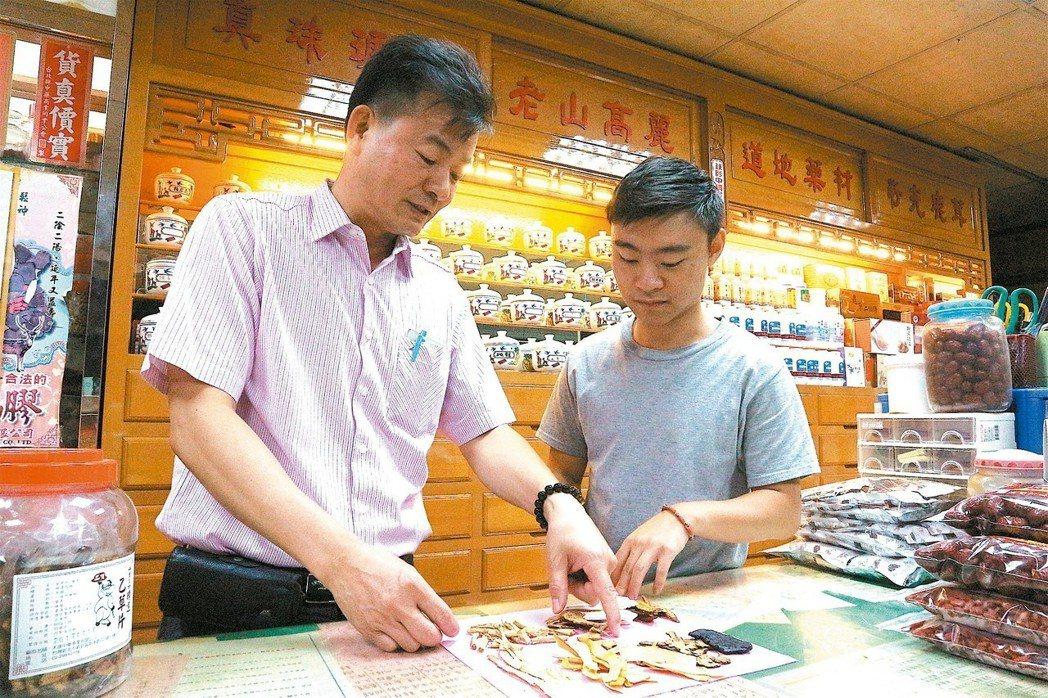 中藥行老闆吳鴻貞(左)教兒子辨認中藥材,憂心家業無法交棒。 記者陳雨鑫/攝影