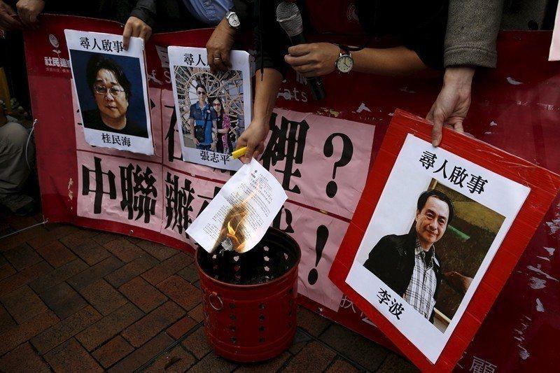 2016年1月,香港抗議人士在中聯辦前手持失蹤的銅鑼灣書店老闆和員工照片,要求中...