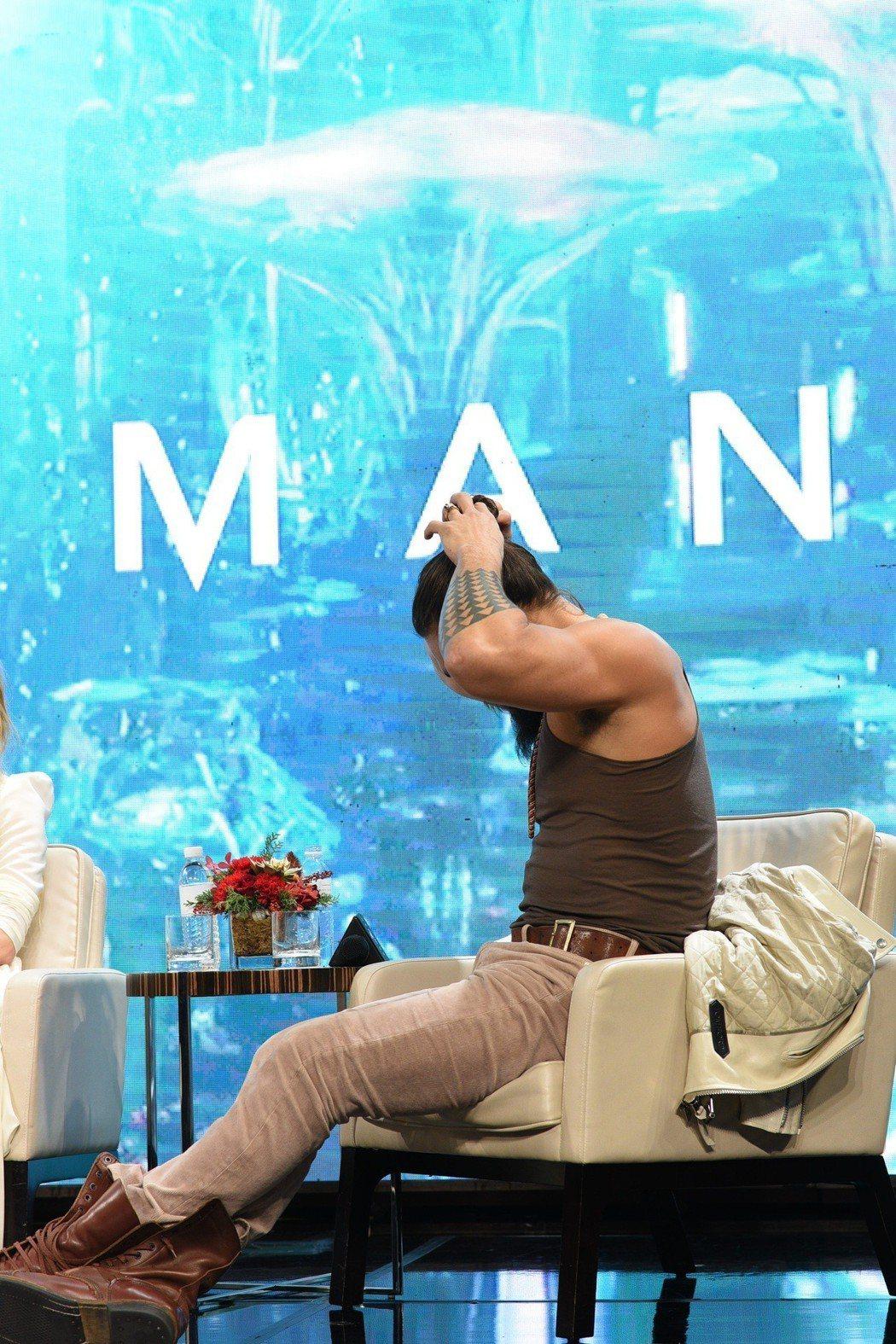 傑森摩墨亞在「水行俠」馬尼拉記者會上突然脫去外套整理頭髮,展現壯碩肌肉。圖/華納...