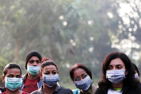 印度空汙嚴重,加爾各答民眾戴有標語的口罩上街抗議。圖/歐新社