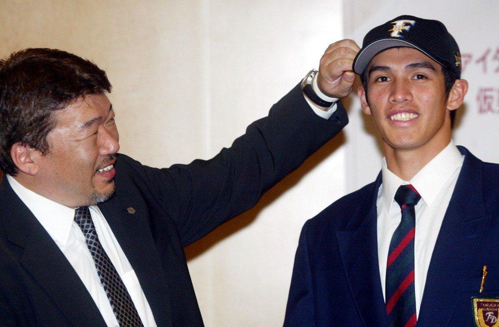 2005年,陽仲壽(右)與日本火腿隊簽約,火腿隊島田利正幫他戴上隊帽。 圖/聯合報系資料照