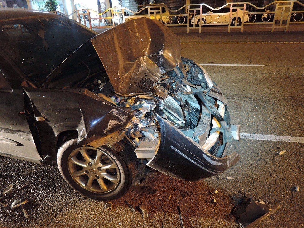 昨晚一輛黑色轎車車頭「卡」在豐原客運55路底盤下,黑色轎車車頭嚴重變形。記者林佩...