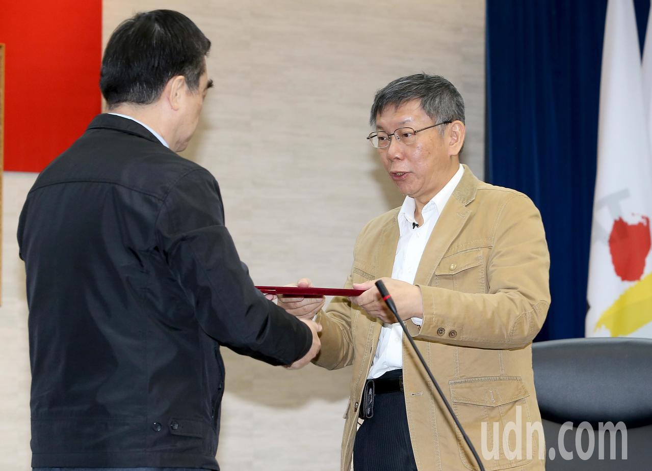 台北市副市長鄧家基(左)上午擔任總辭代表,率市府內閣團隊向台北市長柯文哲(右)遞...