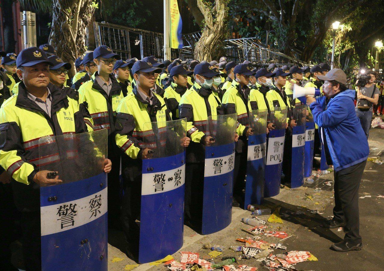 一名陳抗者拿著大聲公喊話,前面則圍著嚴陣以待的值勤員警。 圖/聯合報系資料照片