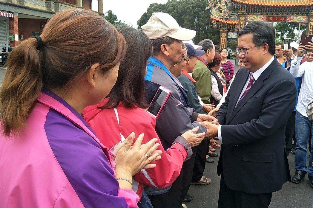 桃園市長鄭文燦(右一)藍綠通吃,成功連任後返回八德故鄉,受到鄰里長輩歡迎。  ...