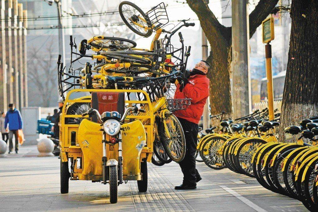 北京街上,電動三輪車騎士把一輛輛ofo的黃色共享單車疊上車帶走。 (法新社)